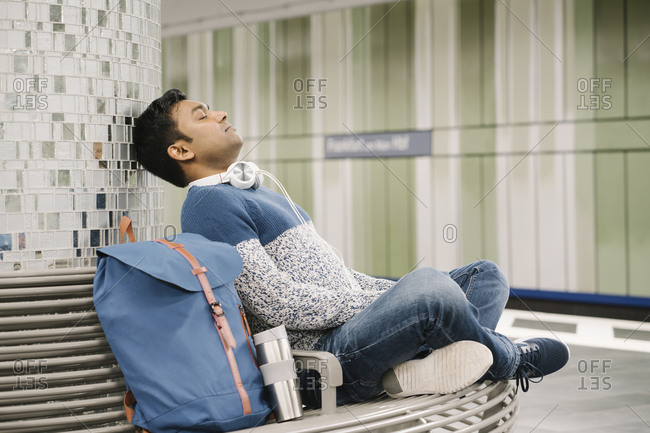 Man relaxing on a bench in subway station