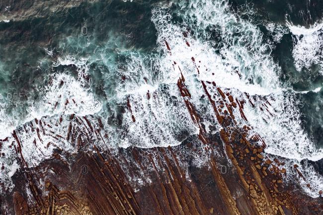 Spain- Biscay- Bilbao- Aerial view of ocean waves brushing against rocky coastline