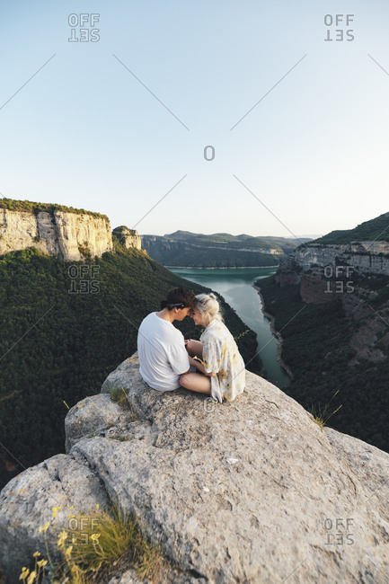 Young couple in love sitting on viewpoint- Sau Reservoir- Catalonia- Spain