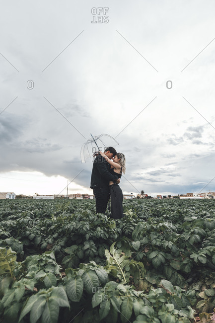 Young couple with transparent umbrella standing in a field hugging each other- Alboraya- Spain