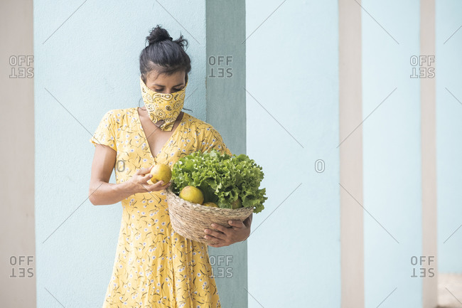 Woman wearing mouth cloth holding basket with salad and fresh fruits