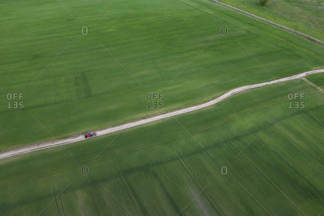 Germany- Brandenburg- Dirt road cutting through vast green countryside field