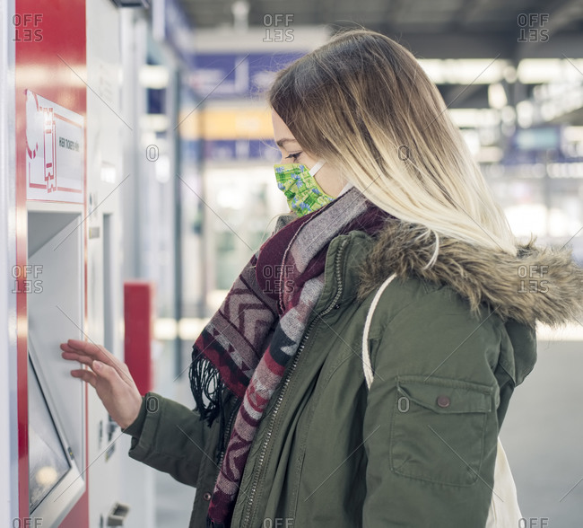 Young woman wearing mask using ticket machine at the station
