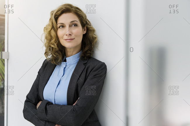 Successful businesswoman leaning on wall- with arms crossed