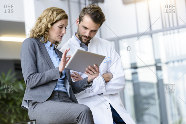 Businesswoman with tablet and doctor talking in hospital