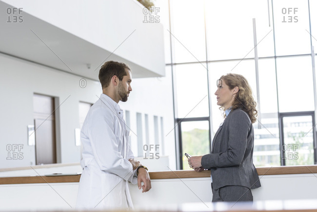Businesswoman and doctor talking in hospital
