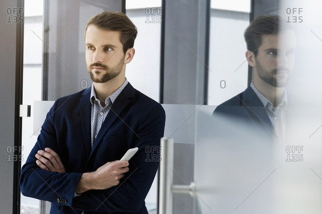 Portrait of young businessman with smartphone looking at distance