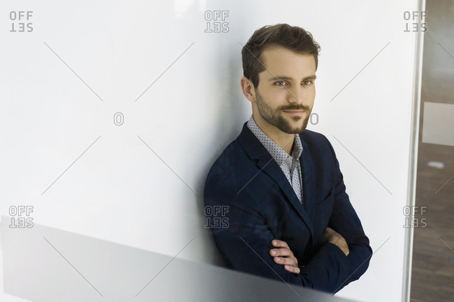 Portrait of smiling young businessman leaning against looking at distance