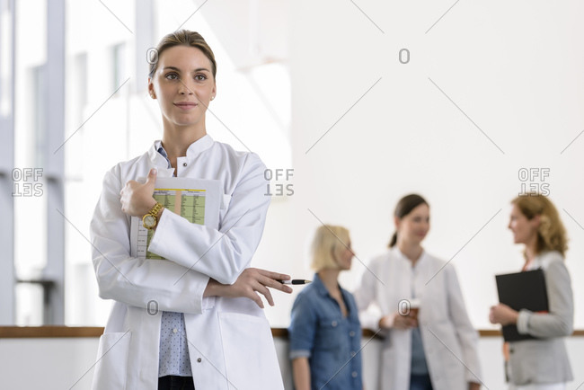 Portrait of female doctor in hospital with colleagues in background