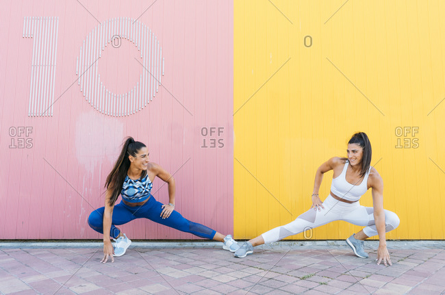 Smiling sportive twins stretching her legs in front of a yellow and pink wall