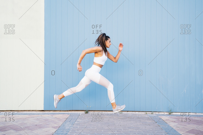Young woman jogging in front of blue and green wall