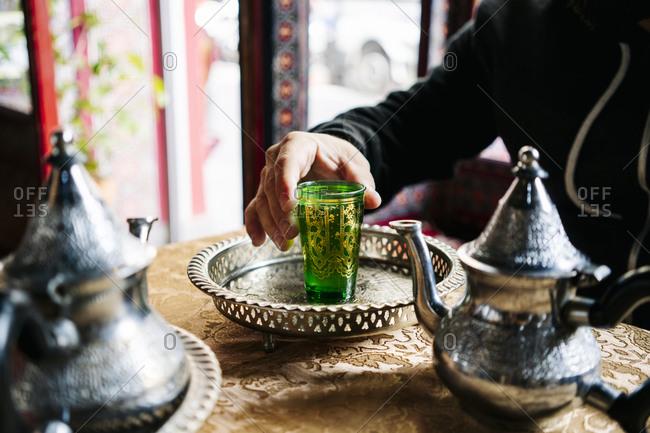 Crop view of man drinking tea in a tea shop