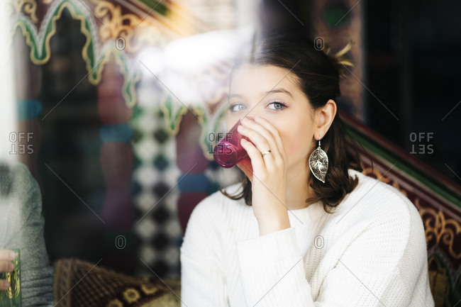 Portrait of young woman drinking tea in a tea shop