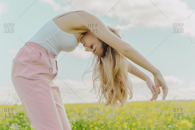 Young woman bending over in a flower meadow in spring