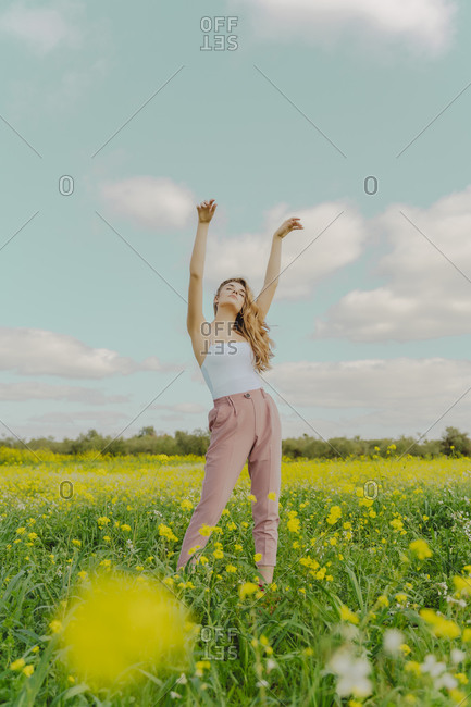 Young woman standing in a flower meadow in spring