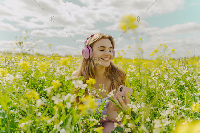 Happy young woman with headphones and smartphone in a flower meadow in spring