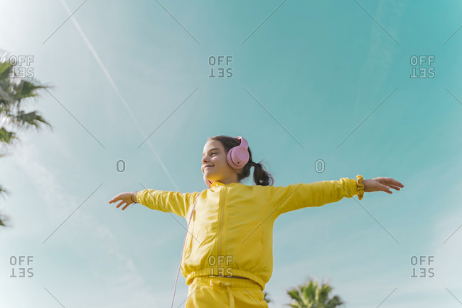 Happy little girl wearing with arms outstretched listening music with headphones outdoors