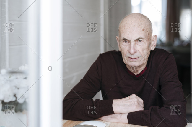 Portrait of pensive old man sitting at table looking out of window