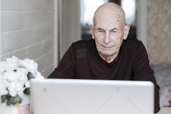 Portrait of an old man looking at laptop