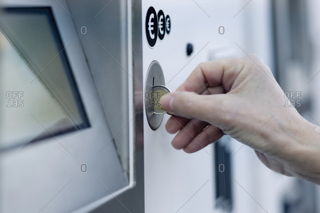 Woman's hand putting coin into pay machine