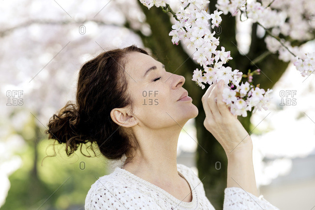 Mature woman with eyes closed smelling blossoms of tree