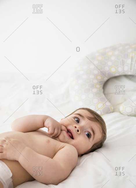 Baby boy lying in bed with finger in mouth
