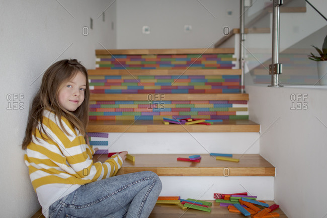 Portrait of girl sitting on stairs and playing with wooden blocks