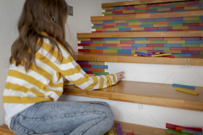 Rear view of girl sitting on stairs and playing with wooden blocks