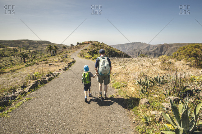 Back view of father and little son with backpacks walking hand in hand on country road- La Gomera- Canary Islands- Spain