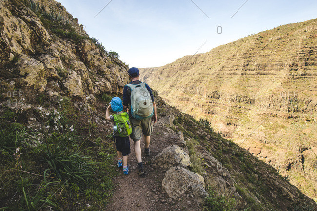 Back view of father and little son with backpacks walking on a hiking trail in the mountains- La Gomera- Canary Islands- Spain