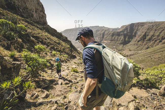 Father and little son with backpacks walking on a hiking trail in the mountains- La Gomera- Canary Islands- Spain