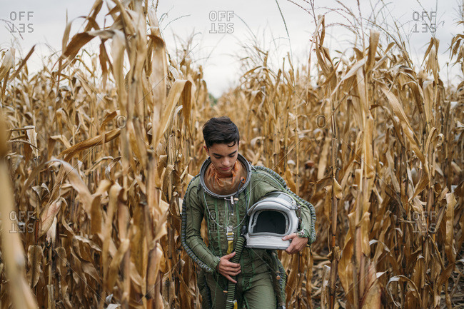Young spaceman walking through corn field