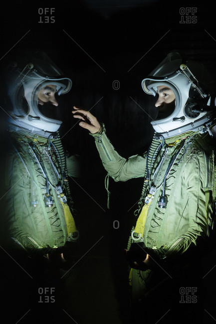 Young spaceman touching his reflection in the dark