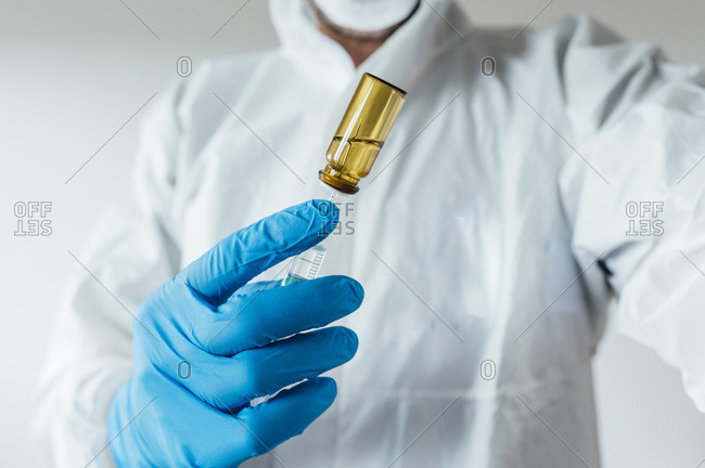 Laboratory technician wearing protective wear- holding vaccine