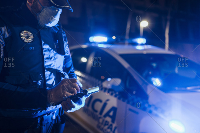 Policeman during emergency mission at night- taking notes- wearing protective gloves and mask