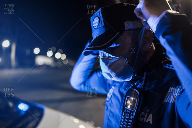 Portrait of policeman wearing mask and protective gloves at night