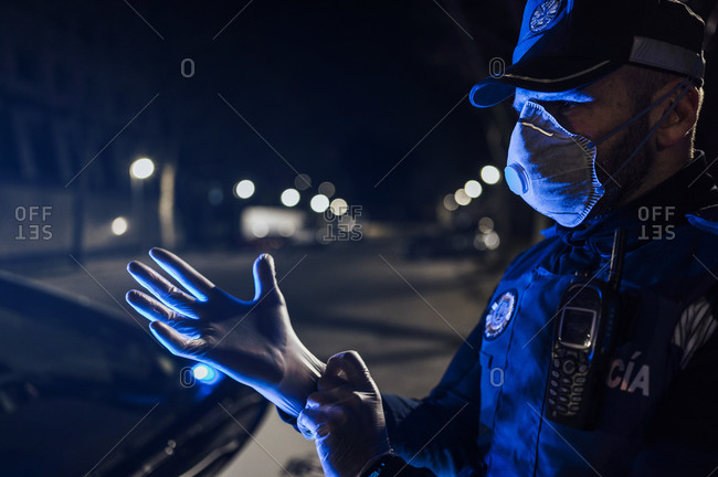 Portrait of policeman wearing mask and protective gloveat night