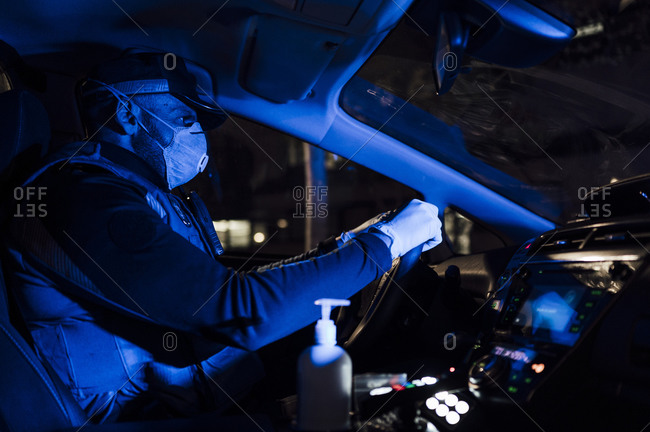 Policeman wearing mask and protective gloves during emergency mission at night