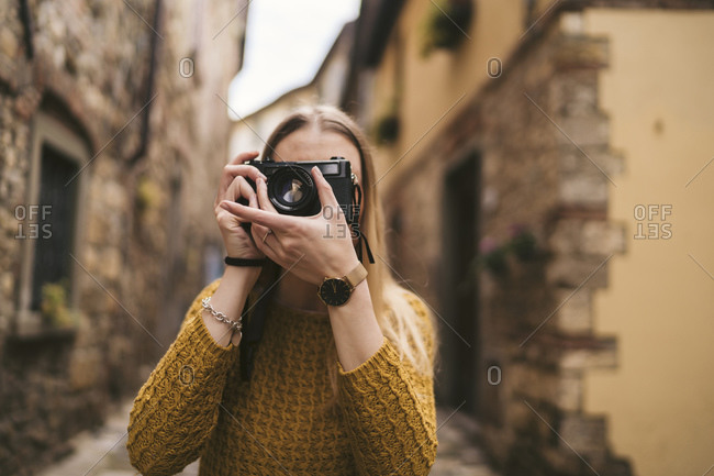 Young woman taking a picture with old-fashioned camera in old town- Greve in Chianti- Tuscany- Italy