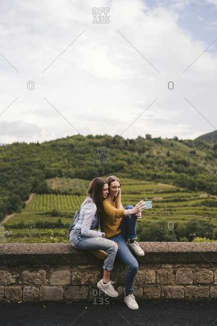 Two young women sitting on a wall in rural landscape taking a selfie- Greve in Chianti- Tuscany- Italy