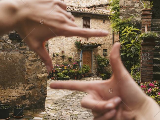 Woman finger framing a house in picturesque old town- Greve in Chianti- Tuscany- Italy