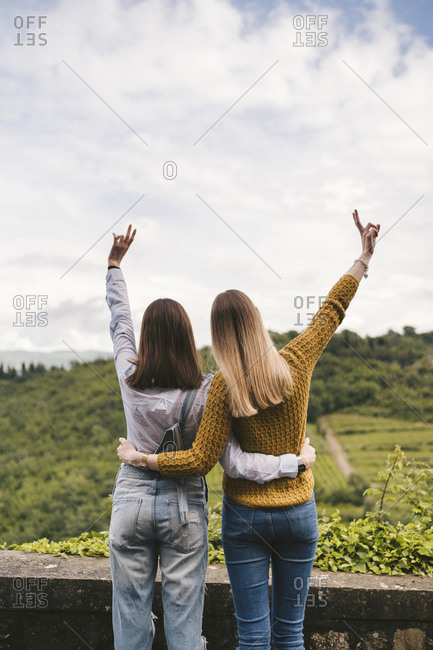 Two happy young women in rural landscape looking at view- Greve in Chianti- Tuscany- Italy