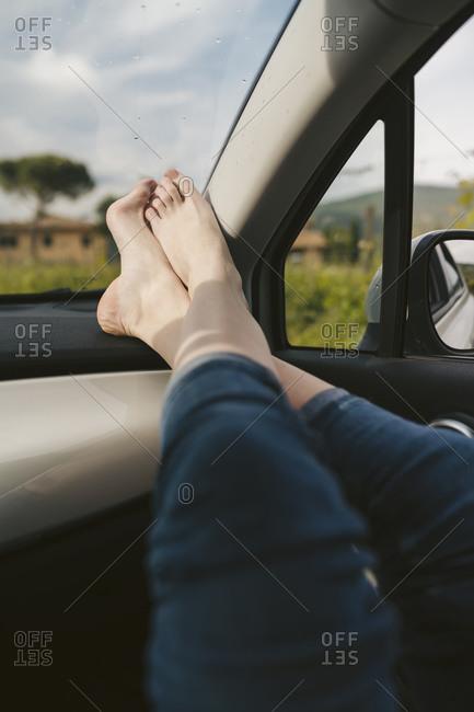 Woman's bare feet in a car