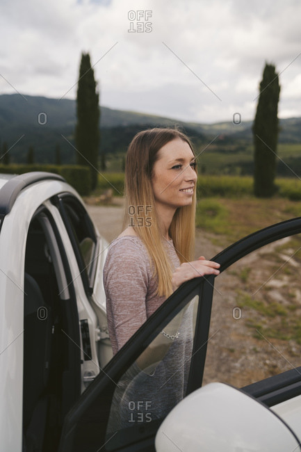 Smiling young woman getting out of car in rural landscape- Tuscany- Italy
