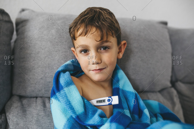 Portrait of sick boy sitting on couch with digital thermometer