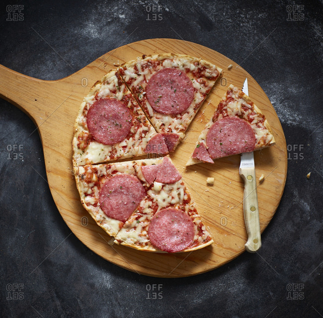 Spatula with slices of salami pizza