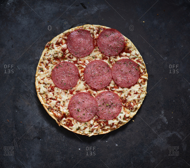 Baked pizza with salami and cheese