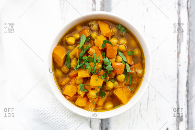 Bowl of oriental pumpkin stew with red kuri squash- roasted turmeric chick-peas and parsley