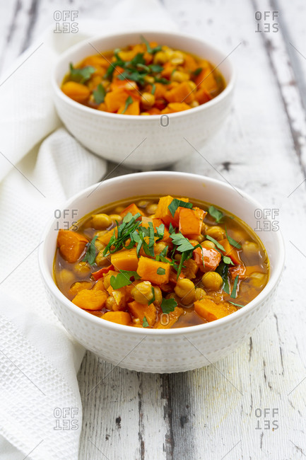 Two bowls of oriental pumpkin stew with red kuri squash- roasted turmeric chick-peas and parsley