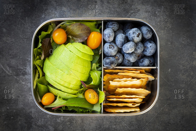 Lunch box with sliced avocado- yellow tomatoes- crackers- blueberries and green salad